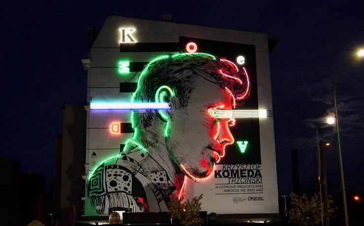 Mural z wizerunkiem Krzysztofa Komedy rozświetlony neonem